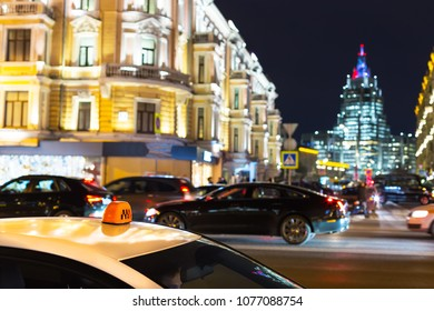 Moscow night traffic and architecture with a taxi car in foreground