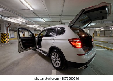 MOSCOW - NOV 17, 2017: White BMW car with open driver and boot doors standing at underground parking, side view.