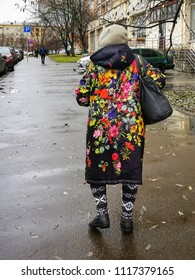 MOSCOW – NOVEMBER 12, 2017: Old woman dressed in bright pattern coat with black bag goes on sidewalk at on November 12, 2017 in Moscow.