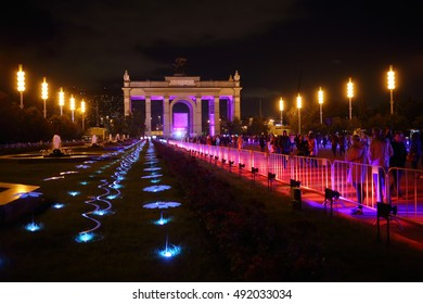 MOSCOW - OCT 1, 2015: People walk at VDNKH near Main entrance arch with illumination