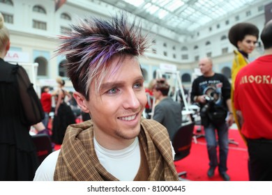 """MOSCOW - OCTOBER 2: Man with original hairstyle with violet strand at XVII International Festival """"World of Beauty - 2010"""" in exhibition complex Gostiny Dvor, on October 2, 2010 in Moscow, Russia."""