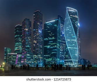 Moscow - October 21, 2018: Night, panoramic view of the Moscow-City International Business Center. People stand on the waterfront and admire the majestic skyscrapers