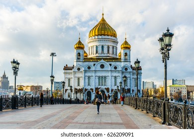 MOSCOW, OCTOBER 29, 2013: Unidentified, unrecognizable people cross Patriarch's pedestrian bridge over the Moscow river in front of Cathedral of Christ the Savior in autumn evening.
