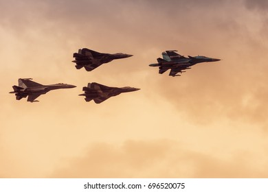 Moscow Region - July 21, 2017: Modern Russian strike fighters Sukhoi Su-35, Su-34 and two newest Su-57 are in the sky at MAKS, Russia. Group of Air Force planes by Sukhoi flies in the sunset light.