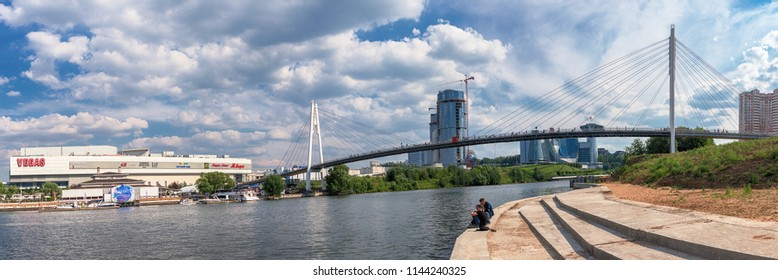 Moscow Region. June 29, 2018. People rest on the embankment of the Moscow River and look at the Pavshinsky Bridge, Crocus City Exhibition Complex, Vegas Shopping Center and the Government House