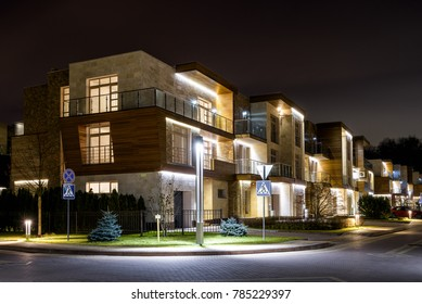 Moscow Region - Nov 13, 2017: Street with townhouses in night town or village. Residential small buildings at dusk. Beautiful LED lighting of modern townhouses. Contemporary houses in evening.