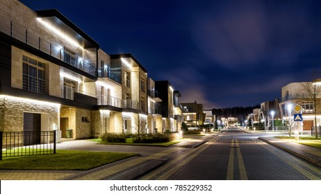 Moscow Region - November 13, 2017: Street with townhouses in night town. Modern residential houses in evening. Beautiful lighting of townhouses at dusk. Panorama of illuminated small city or village.