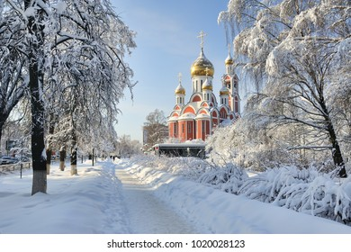 MOSCOW REGION, RUSSIA - The Church of St. George the Victorious framed by trees covered with thick layer of snow after blizzard on a nice sunny winter day in the city center of Odintsovo city.