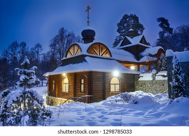 MOSCOW REGION, RUSSIA - Covered snow illuminated wooden house-chapel with a font above the Holy Spring of St. Savva (Sabbas) Storozhevsky framed by spruce trees in winter twilight in Zvenigorod