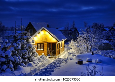 MOSCOW REGION, RUSSIA - Illuminated Little Russian Wooden House-Banya After the Blizzard in Twilight.