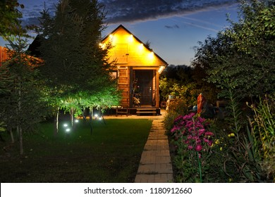 MOSCOW REGION, RUSSIA - Illuminated Russian Dacha in Twilight. Little wooden guest house-banya with line of spruce trees at night time on one nice  Autumn morning with beautiful twilight skies.