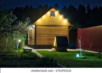 MOSCOW REGION, RUSSIA - View from a garden area on the backside of illuminated wooden guest house-banya with a well in the background of tall pine trees when it was getting dark in the springtime.