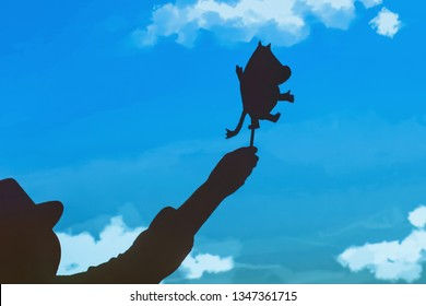 Moscow region / Russia-01 03 2019: Puppet theater silhouettes of Moomin trolls. Doll in hand behind the curtain. Silhouette Mumiy Troll keeps actor puppeteer