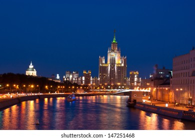 The Moscow river, Stalin High-rise, buildings and bridges in evening lights.