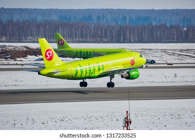 Moscow / Russia - 02.26.2018. Domodedovo International Airport.  Passenger plane Airbus A319 of S7 Airlines (Sibir Airlines) takes off from airport runway. Tanks with aviation fuel in the background.