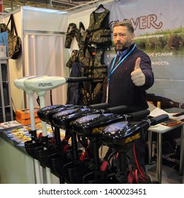 Moscow / Russia – 03 02 2019: Lucky manager on display stand Flover with new transom trolling electric outboard motors on exhibition Hunting and fishing - 2019 at VDNH (VVC, ENEA)