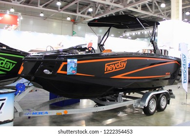 Moscow / Russia – 03 08 2018: Black-orange motor boat Heyday WT-2 with Bimini top awning on 2-axle trailer at the Russian Yacht exhibition Moscow Boat show MBS 2018 in Crocus Expo
