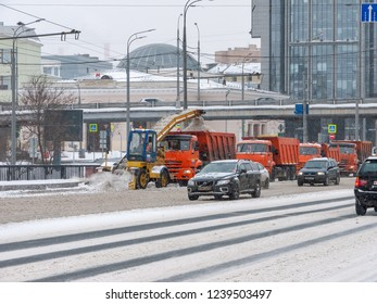 Moscow / Russia - 03.04.2018: Tractor removes snow from the road in an orange truck KAMAZ