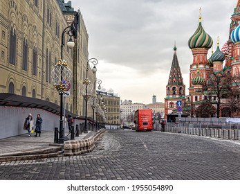 Moscow, Russia, 03.18.2021. Descent to the Kremlin Embankment, the domes of St. Basil's Cathedral, a red tourist bus and lonely tourists during the coronavirus epidemic