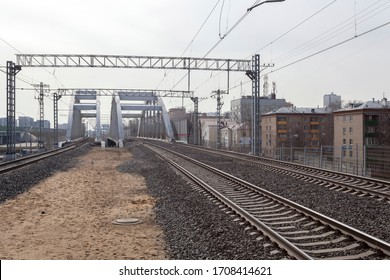 Moscow, Russia - 03/27/2020: The railroad with some electric wires and cables over it coming through the city on the background of buildings.