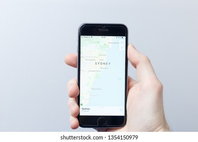 Moscow / Russia - 03.30.2019:  A hand holding a smartphone which displays city map with SYDNEY. Illustrative editorial image on an white background. Travel concept