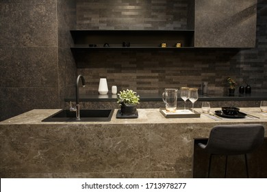 MOSCOW / RUSSIA -  04/03/2019 luxurious spacious modern kitchen island in black grey brown stone marble tones, a sink, a comfortable dining area. a table, wine glasses, plates on the counter top