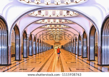 Moscow Russia, 05 august 2016, beautiful subway station with modern architecture and metro with lonely girl red dress walking between columns.