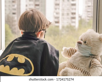 Moscow,  Russia -05.06.2020: A medical masked teddy bear and an uncertain boy in a Batman costume by the window  stay at home in self-quarantine.