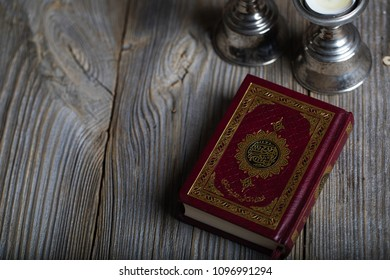 Moscow, Russia. 05/21/2018: Quran and candles on a wooden surface. Translation into English - the book contains verses of Koran