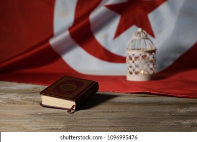Moscow, Russia. 05/21/2018. Sacred book of Koran on a wooden surface. Tunisian flag in the background. Translation - the book contains verses of Koran
