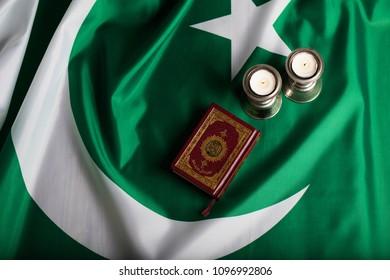 Moscow, Russia. 05/21/2018:Quran and candles on a flag of Pakistan. Translation into English - the book contains verses of Koran