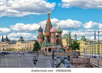 Moscow, Russia, 05.25.2021. View of the domes of St. Basil's Cathedral, Red Square, GUM building and Vasilievsky Descent against the blue sky with clouds