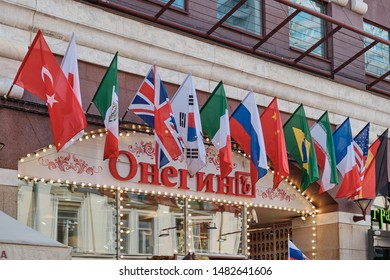 """Moscow \ Russia 06 10 2019: Flags of different countries of the world over the Onegin restaurant on Arbat street. Restaurant """"Onegin"""" in the domain of the Central street of Moscow."""