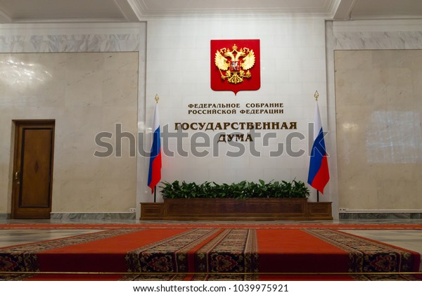 """Moscow, Russia - 06.11.2014. Interior of the State Duma (Parliament) of the Russian Federation. An inscription """"Federal Assembly of the Russian Federation. State Duma"""" and the state emblem and flags"""