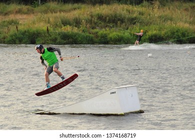 Moscow / Russia – 08 22 2017: Wakeboarder jump on springboard on the wake board in the Wakeboard club Strogino in summer day