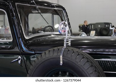 Moscow / Russia – 08 31 2016: The rear view mirror and a spare wheel on the front wing of the old black car  at exhibition Moscow International Automobile Salon MMAS 2016 in Crocus Expo, motor show