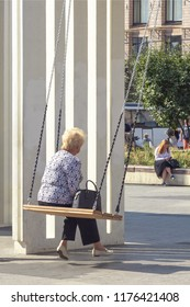 Moscow, Russia, 09.07.2018. A gray-haired elderly woman, in a jacket and with a handbag, sitting and swinging on a swing