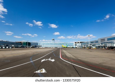 Moscow / Russia - 10.04.2018. Domodedovo International Airport. Passenger terminal and Air Traffic Control Tower (ATC Tower). Blue sky in the background.