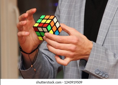 Moscow / Russia - 11 20 2018: The hands of intelligent illusionist men of the businessman in the grey suit assemble the Rubik's cube close-up - the symbol of finding solutions, consolidation, creativy