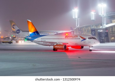 Moscow / Russia - 12.26.2018. Vnukovo International Airport during snow storm. Passenger aircraft Sukhoi Superjet 100 of Azimuth Airlines taxiing on the airport runway.