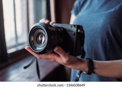 MOSCOW, RUSSIA - 14 MARCH 2019: Fujifilm GFX50s Camera, Fujifilm Mirrorless. Close-up of hand holding camera. Mirrorless camera close up in the hand of a young woman on a studio background.