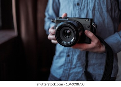 MOSCOW, RUSSIA - 14 MARCH 2019: Fujifilm GFX50s Camera, Fujifilm Mirrorless. Close-up of hand holding camera. Mirrorless camera close up in the hand of a young man on a studio background.