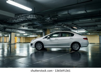 Moscow, Russia - 15 July, 2018 white Peugeot 408 sedan parked in the empty underground parking of the mall.