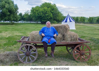 Moscow/ Russia - 16.06.2019: cheerful man in medieval blue clothes is sitting on a horse-drawn cart on the background of a green meadow with an ancient historical tent. festival Vremena i Epohi