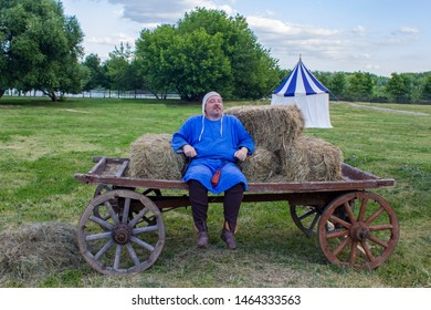 Moscow/ Russia - 16.06.2019: a contented man in medieval blue clothes is sitting on a horse-drawn cart on the background of a green meadow with an ancient historical tent. festival Vremena i Epohi