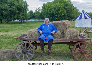Moscow/ Russia - 16.06.2019: Kindly man in medieval blue clothes sits on a horse-drawn cart against the background of a green meadow with an ancient historical tent. festival Vremena i Epohi