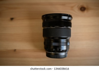 MOSCOW, RUSSIA - 17 MARCH 2019: Fuji LENS. the camera lens on light wooden table, Top view. Flat lay style. Close up.