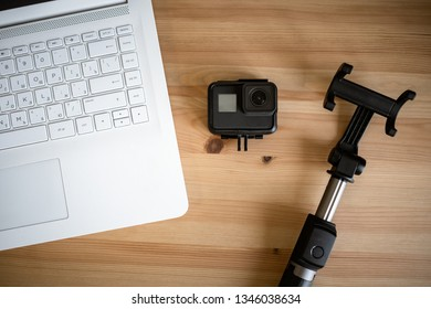 MOSCOW, RUSSIA - 17 MARCH 2019: Work space on table of photographer. Minimal workspace with Laptop and GO-pro camera on wooden background. Top view. Flat lay style. Close up
