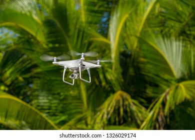 MOSCOW, RUSSIA - 2 October, 2017: a Phantom 4 Pro drone in flight, green trees in the background, selective focus on the drone. Phantom 4 Pro is a drone manufactured by the DJI company.