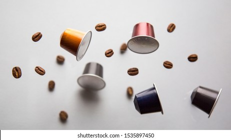 MOSCOW, RUSSIA - OCTOBER16, 2019: Nespresso Coffee Capsule and Coffee Beans Flying on Neutral Background. Nespresso is Worldwide Company of Coffee Products. Natural Light. Selective Focus.